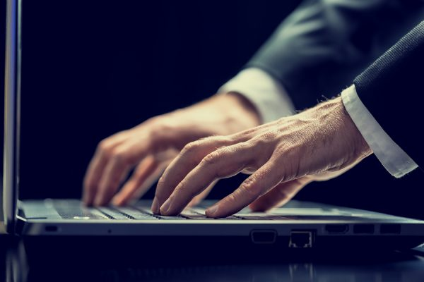 Close up low angle view of a businessman typing on a laptop computer in darkness conceptual of a dedicated employee working late or of a hacker stealing data and information.
